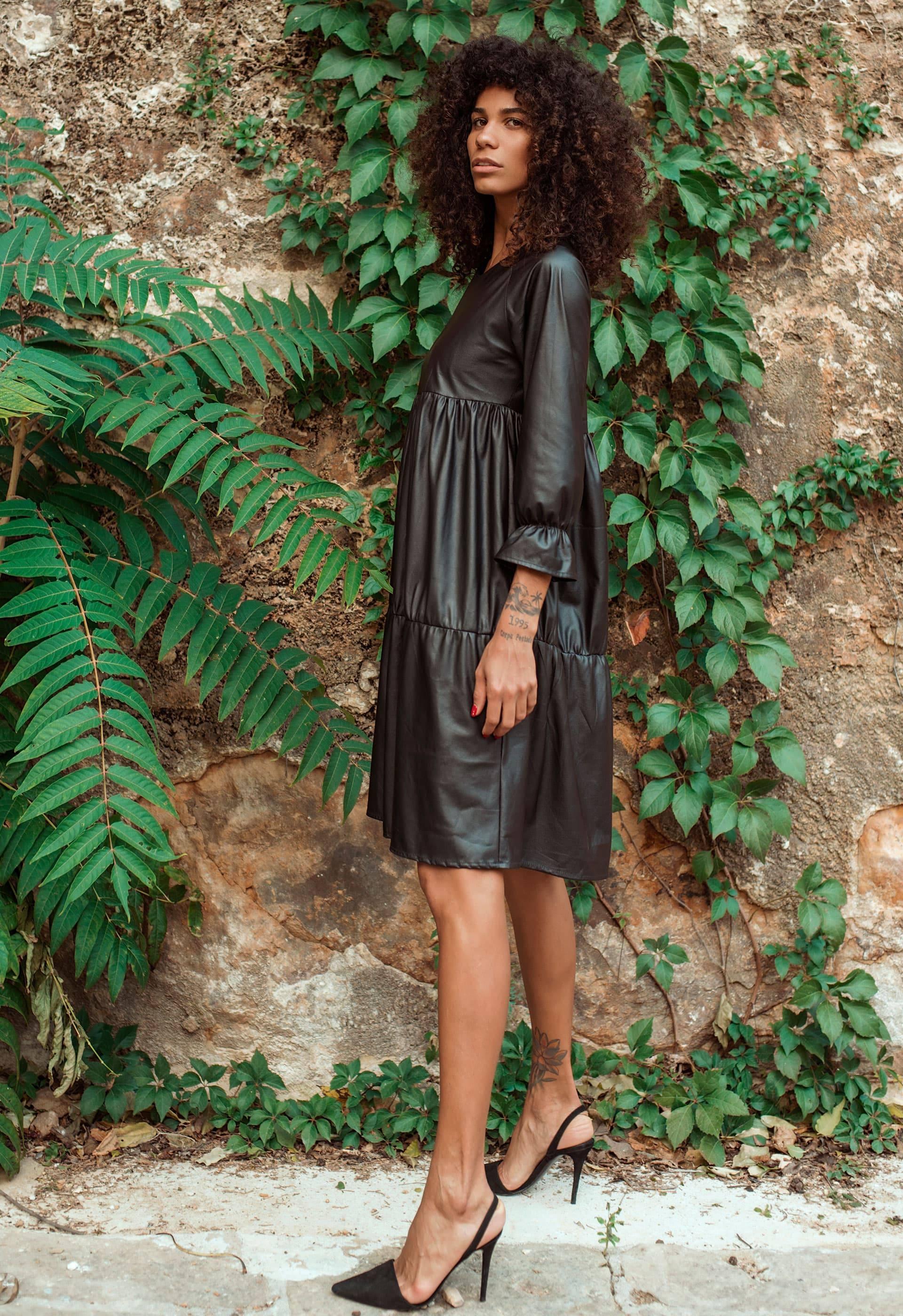 Vestido negro simil piel negro con puño fruncido en volante.